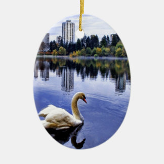 White Swan Swimming In The City Ceramic Oval Ornament