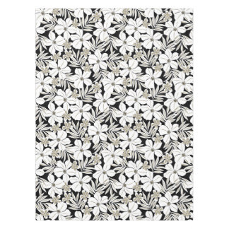 White tropical flowers on black tablecloth