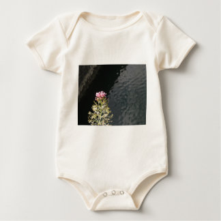 Wildflowers against the water surface of a river baby bodysuit