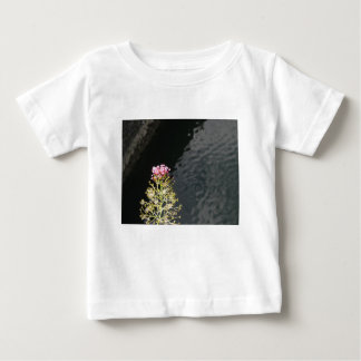 Wildflowers against the water surface of a river baby T-Shirt