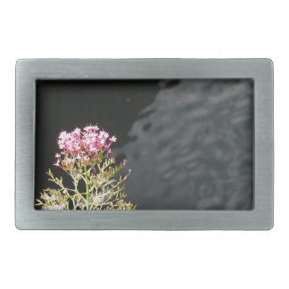 Wildflowers against the water surface of a river rectangular belt buckle
