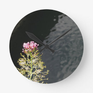 Wildflowers against the water surface of a river round clock