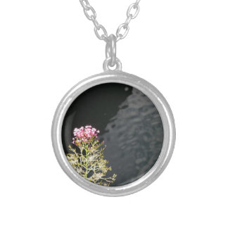 Wildflowers against the water surface of a river silver plated necklace