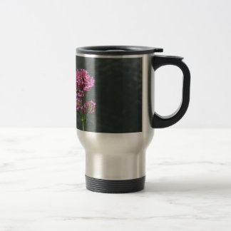 Wildflowers against the water surface of a river travel mug