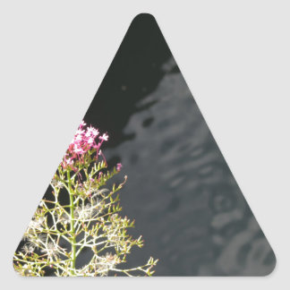 Wildflowers against the water surface of a river triangle sticker