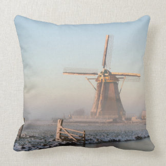 Windmill in the snow at sunrise throw pillow