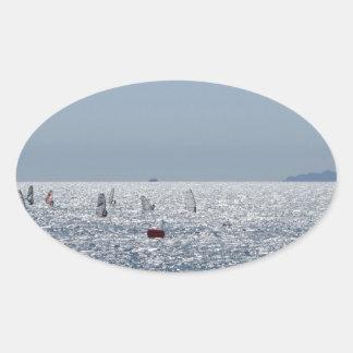Windsurfing in the sea . Windsurfers silhouettes Oval Sticker