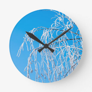 Winter tree branches covered with frost snow round clock
