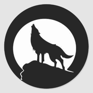 Wolf howling with a full moon round sticker