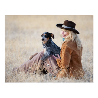 Woman and dog sitting in field postcard