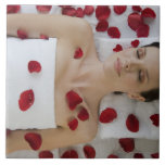 Woman covered in flower petals laying on massage tile