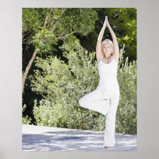 Woman doing yoga on patio poster