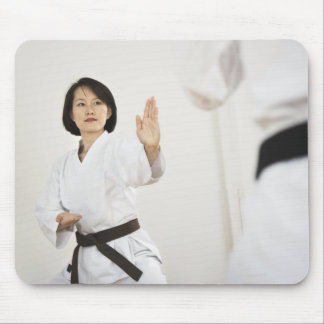 Woman fighting in karate competition mouse pads