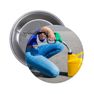 Woman filling yellow can with gasoline or petrol. 2 inch round button