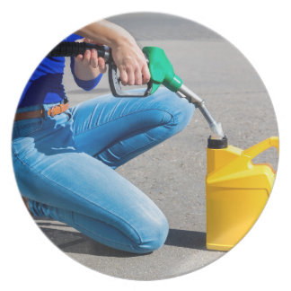 Woman filling yellow can with gasoline or petrol. dinner plate