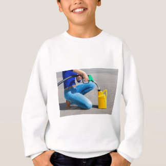 Woman filling yellow can with gasoline or petrol. sweatshirt