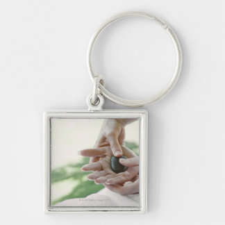 Woman getting hand massage with hot stone Silver-Colored square keychain