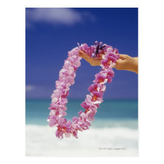 Woman holding Floral lei by beach, Close-up of Postcard