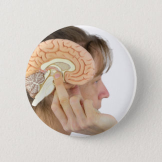 Woman holding hemisphere model  against head 2 inch round button
