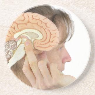 Woman holding hemisphere model  against head coaster