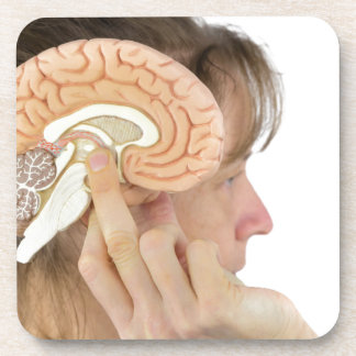 Woman holding hemisphere model  against head drink coasters