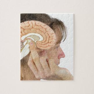 Woman holding hemisphere model  against head jigsaw puzzle