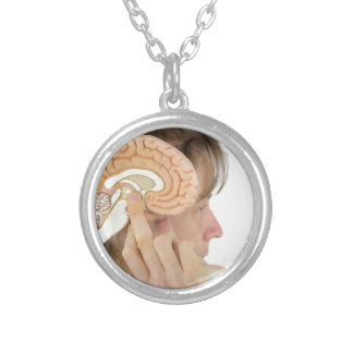 Woman holding hemisphere model  against head silver plated necklace