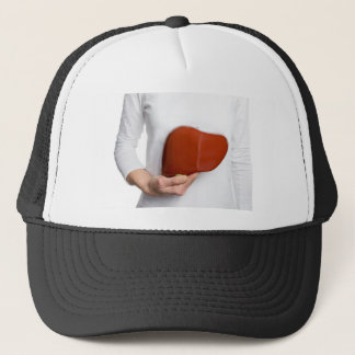 Woman holding human liver model at white body trucker hat