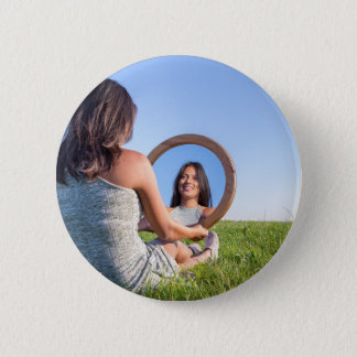 Woman in nature viewing her mirror image 2 inch round button