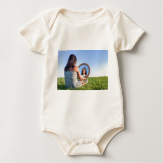 Woman in nature viewing her mirror image baby bodysuit
