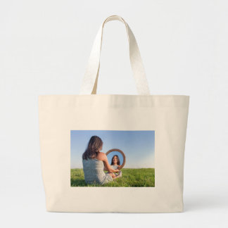 Woman in nature viewing her mirror image large tote bag