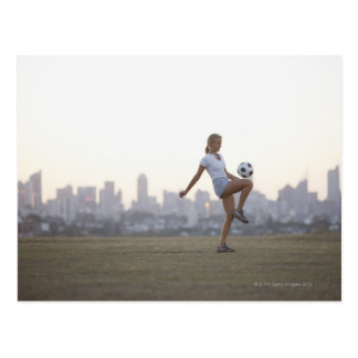 Woman kneeing soccer ball in urban park postcard