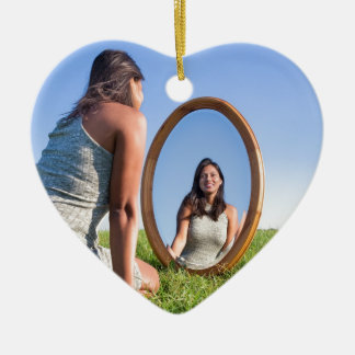 Woman kneeling on grass looking at mirror image ceramic heart ornament