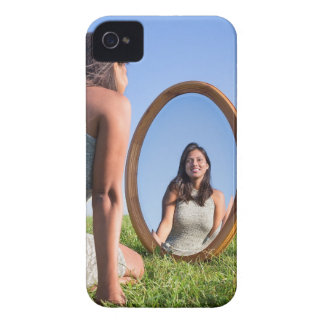 Woman kneeling on grass looking at mirror image iPhone 4 covers