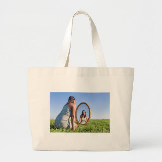 Woman kneeling on grass looking at mirror image large tote bag