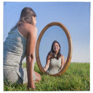 Woman kneeling on grass looking at mirror image napkin