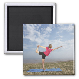Woman practicing yoga by the beach square magnet
