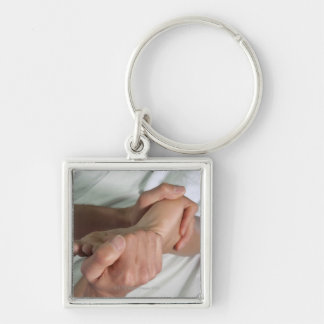 Woman receiving foot massage 2 Silver-Colored square keychain