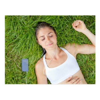 Woman relaxes with music in soft grass postcard