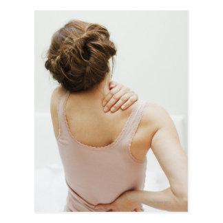 Woman rubbing aching back postcard