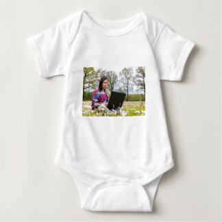 Woman sits with laptop in blooming meadow baby bodysuit