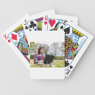 Woman sits with laptop in blooming meadow bicycle playing cards