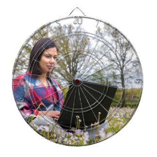 Woman sits with laptop in blooming meadow dartboard