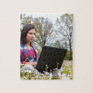 Woman sits with laptop in blooming meadow jigsaw puzzle