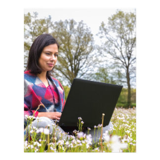 Woman sits with laptop in blooming meadow letterhead