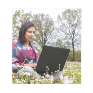 Woman sits with laptop in blooming meadow notepads