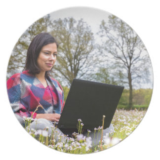 Woman sits with laptop in blooming meadow plate