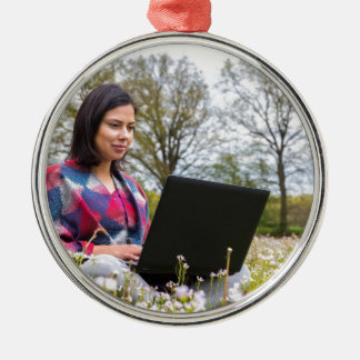 Woman sits with laptop in blooming meadow Silver-Colored round ornament