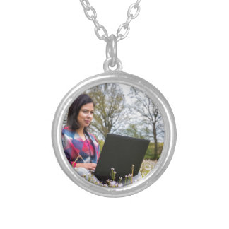 Woman sits with laptop in blooming meadow silver plated necklace