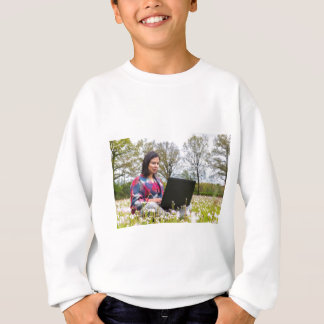 Woman sits with laptop in blooming meadow sweatshirt